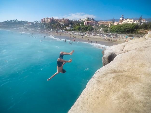 Adolescente che salta sul mare vicino alle rocce con alcune persone che lo guardano - attività molto pericolosa e ragazzo che fa backflip e più freestyle