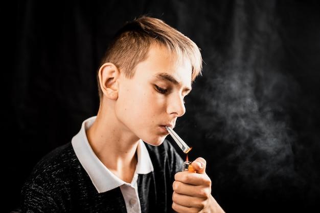 Un adolescente che accende una sigaretta o una droga è un dollaro arrotolato, il concetto di dipendenza da adolescenti e spendere soldi orrore