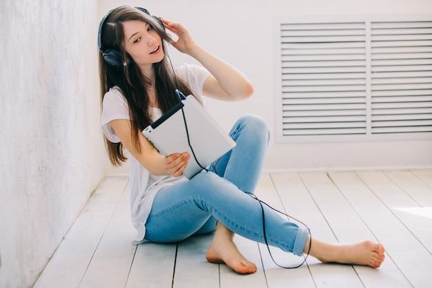 L'adolescente ascolta la musica seduto sul pavimento
