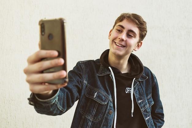 Un adolescente fa un selfie con il suo telefono su uno sfondo chiaro - il giovane felice scatta una foto di se stesso con un telefono
