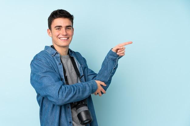 Uomo del fotografo dell'adolescente isolato su fondo blu che indica dito il lato