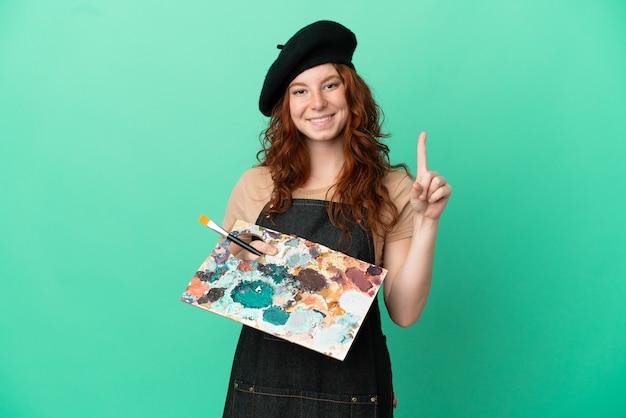 Artista adolescente dai capelli rossi che tiene una tavolozza isolata su sfondo verde che mostra e solleva un dito in segno del meglio