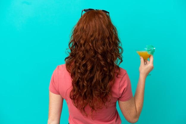 Adolescente ragazza rossa con cocktail isolato su sfondo blu in posizione posteriore