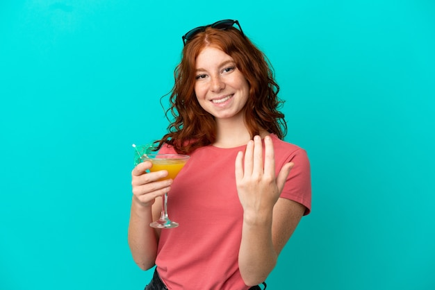 Adolescente ragazza rossa con cocktail isolato su sfondo blu che invita a venire con la mano. felice che tu sia venuto
