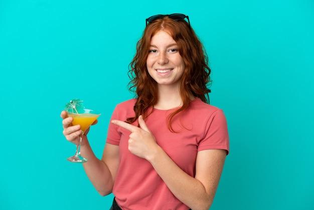 Adolescente ragazza rossa con cocktail isolato su sfondo blu e puntandolo