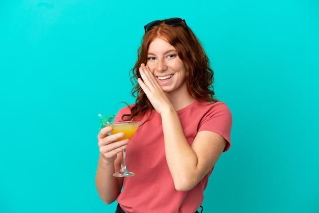 Adolescente rossa ragazza con cocktail isolato su sfondo blu sussurrando qualcosa