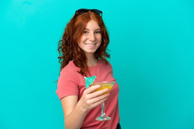 Cocktail della tenuta della ragazza della testarossa dell'adolescente isolato su fondo blu con l'espressione felice