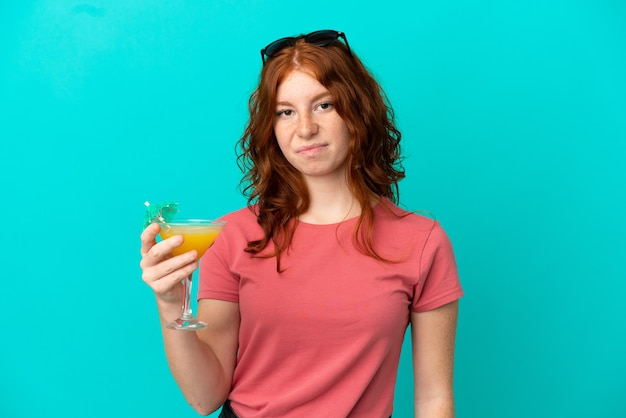 Cocktail della tenuta della ragazza della testarossa dell'adolescente isolato su fondo blu con l'espressione triste