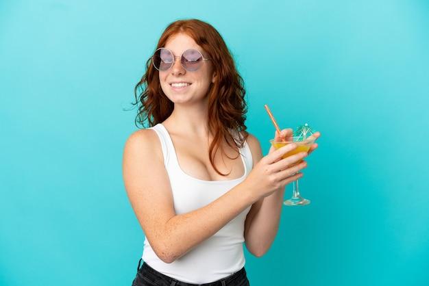 Ragazza rossa dell'adolescente isolata su fondo blu in costume da bagno e che tiene un cocktail