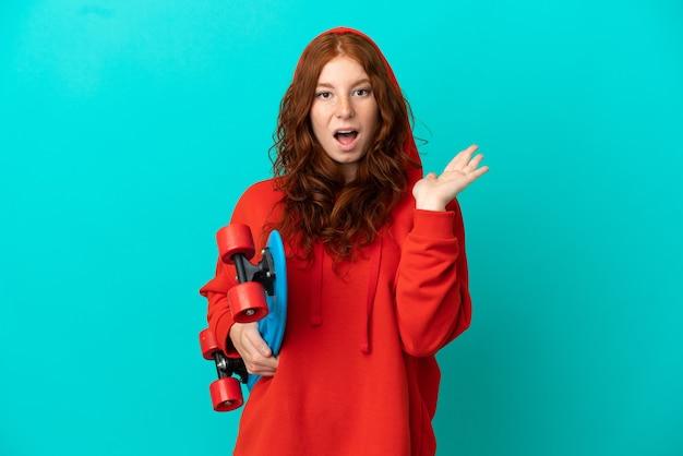 Ragazza rossa dell'adolescente isolata su fondo blu con un pattino e facendo un gesto di sorpresa