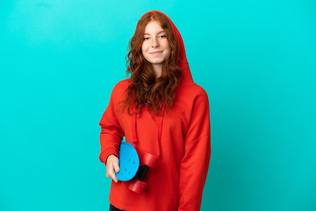 Ragazza adolescente rossa isolata su sfondo blu con uno skate