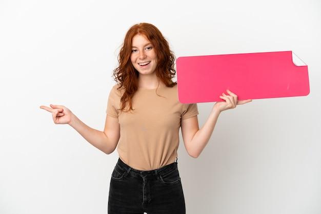 Ragazza rossa dell'adolescente isolata su fondo bianco che tiene un cartello vuoto e che indica side