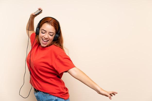 Musica d'ascolto della ragazza di redhead dell'adolescente