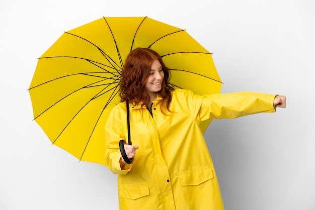Cappotto e ombrello impermeabili della ragazza della testarossa dell'adolescente isolati su fondo bianco che dà un pollice in su gesto