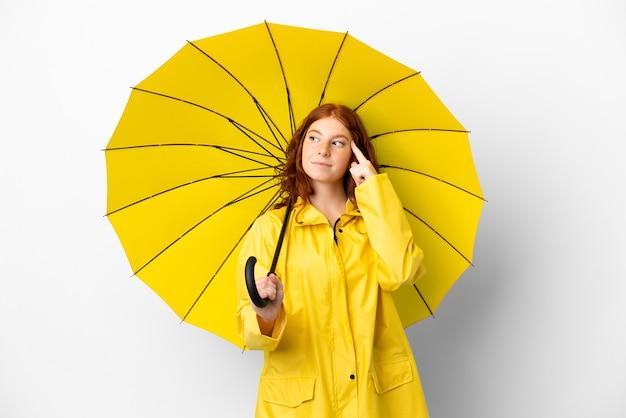 Cappotto e ombrello impermeabili della ragazza della testarossa dell'adolescente isolati su fondo bianco che ha dubbi e pensiero