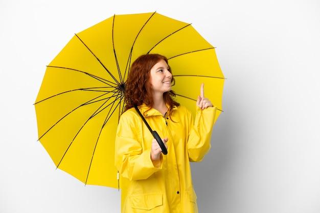 Cappotto e ombrello impermeabili della ragazza della testarossa dell'adolescente isolati su fondo bianco che indica su una grande idea