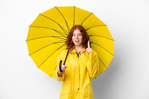 Cappotto e ombrello impermeabili della ragazza della testarossa dell'adolescente isolati su fondo bianco che pensano un'idea che indica il dito su