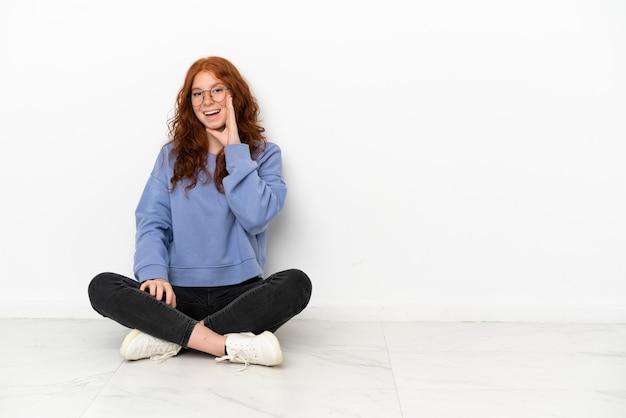 Ragazza rossa dell'adolescente che si siede sul pavimento isolata su fondo bianco che grida con la bocca spalancata