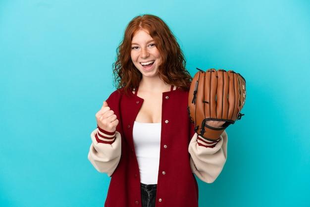 Ragazza adolescente dai capelli rossi con guanto da baseball isolato su sfondo blu che celebra una vittoria nella posizione del vincitore