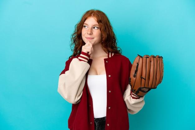 Ragazza adolescente rossa con guanto da baseball isolata su sfondo blu e alzando lo sguardo