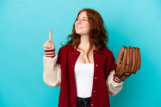 Adolescente ragazza rossa con guanto da baseball isolato su sfondo blu che punta verso l'alto una grande idea