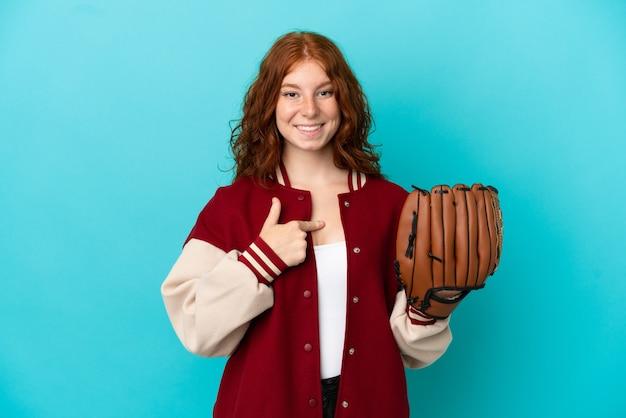 Ragazza rossa dell'adolescente con il guanto da baseball isolato su fondo blu con l'espressione facciale di sorpresa