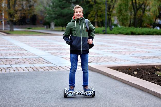 Adolescente che guida il giroscooter nel parco il giorno d'autunno