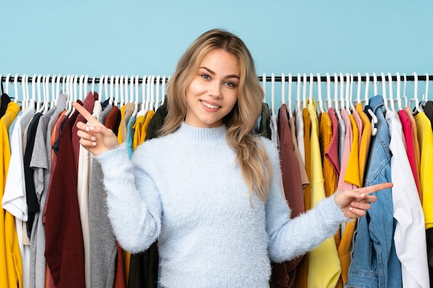 Ragazza russa dell'adolescente che compra alcuni vestiti isolati sulla parete blu che indica il dito ai laterali e felice