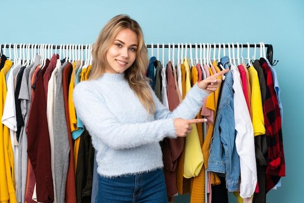 Ragazza russa dell'adolescente che compra alcuni vestiti isolati sulla parete blu che indica il dito a lato e che presenta un prodotto