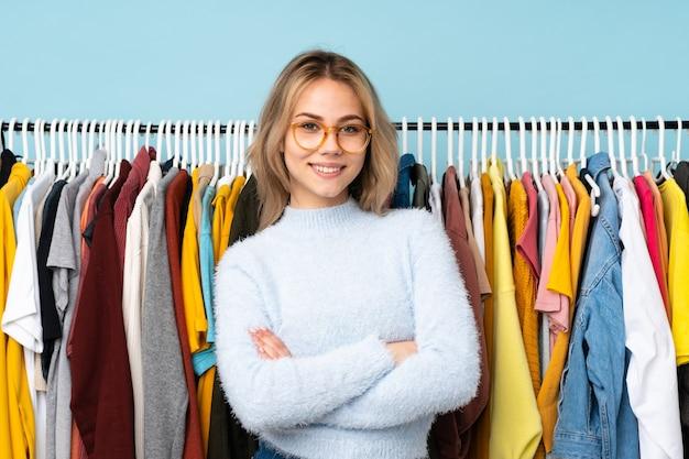 Ragazza russa dell'adolescente che compra dei vestiti isolati sulla parete blu con gli occhiali e sorridente
