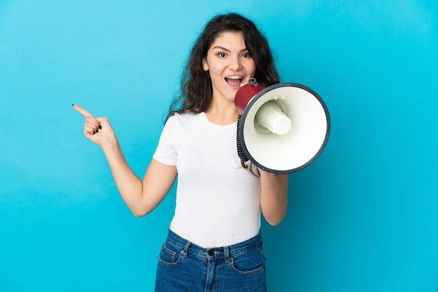 Ragazza russa dell'adolescente isolata su priorità bassa blu che grida tramite un megafono e il lato di puntamento