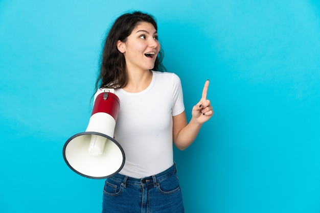Ragazza russa dell'adolescente isolata sulla parete blu che tiene un megafono e che intende realizzare la soluzione