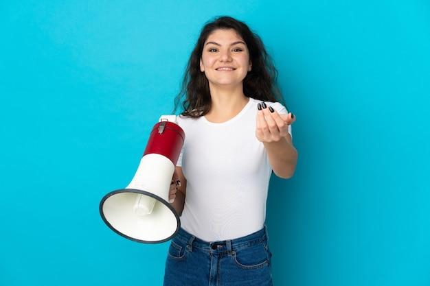 Ragazza russa dell'adolescente isolata che tiene un megafono e che invita a venire con la mano