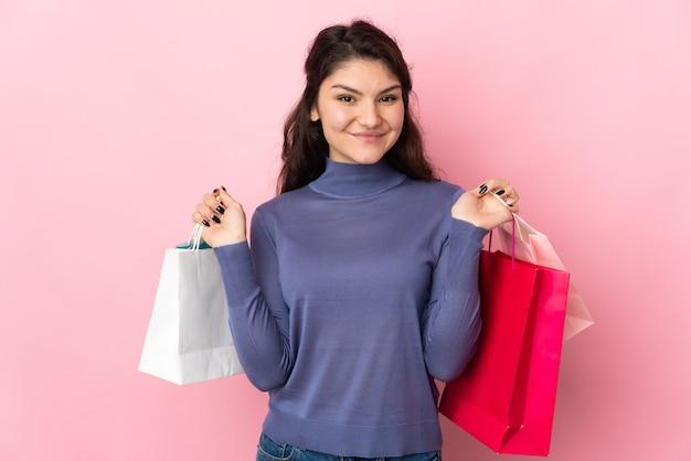 Adolescente ragazza russa isolata su sfondo rosa tenendo le borse della spesa e sorridente