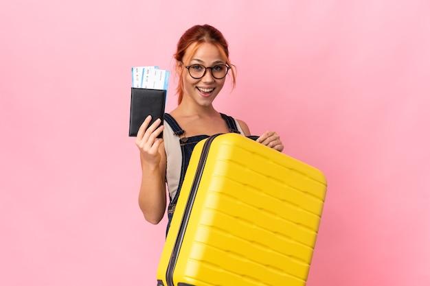 Ragazza russa dell'adolescente isolata sulla parete rosa in vacanza con la valigia e il passaporto