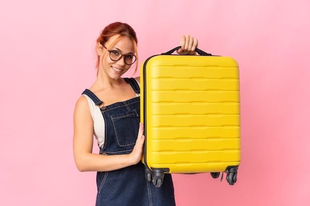 Ragazza russa dell'adolescente isolata sulla parete rosa in vacanza con la valigia di viaggio