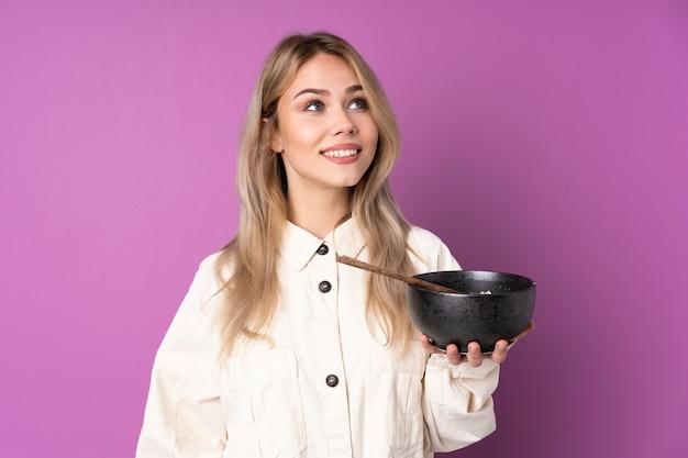 Ragazza russa dell'adolescente isolata sulla porpora che osserva in su mentre sorride mentre tiene una ciotola di tagliatelle con le bacchette