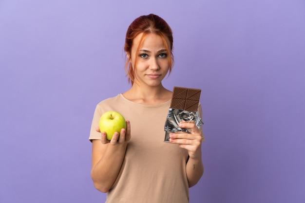 Adolescente ragazza russa isolata sul muro viola prendendo una tavoletta di cioccolato in una mano e una mela nell'altra