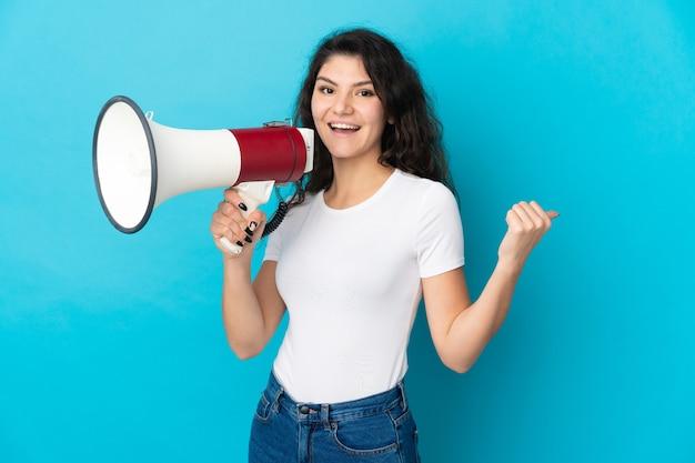Ragazza russa dell'adolescente isolata che grida tramite un megafono e che indica lato