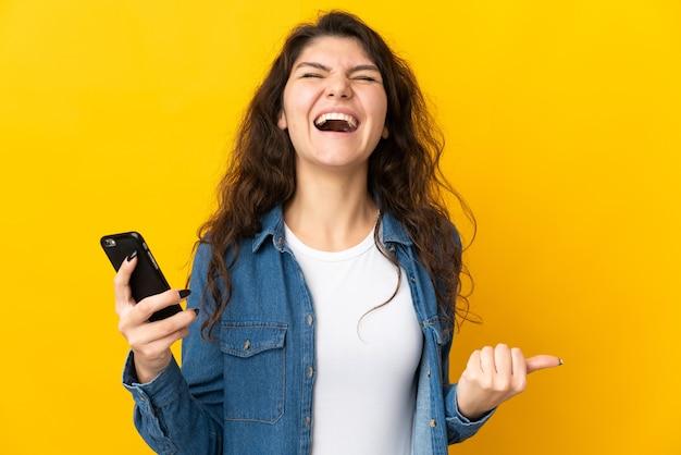 Adolescente ragazza russa isolata utilizzando il telefono cellulare e facendo il gesto di vittoria