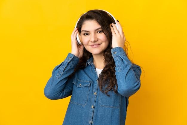 Ragazza russa dell'adolescente isolata sulla musica d'ascolto della parete gialla