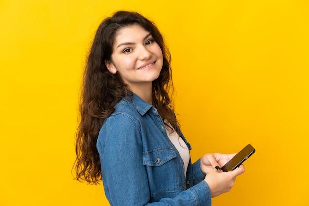 Ragazza russa dell'adolescente isolata sulla parete gialla che invia un messaggio o un'e-mail con il cellulare