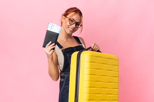 Ragazza russa dell'adolescente sul rosa in vacanza con la valigia e il passaporto