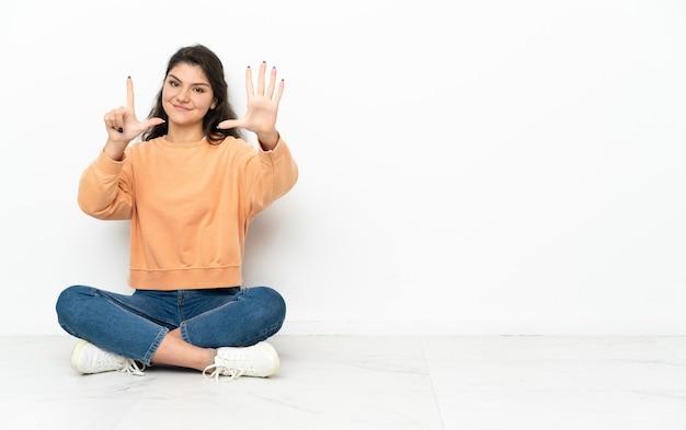 Ragazza russa dell'adolescente che si siede sul pavimento che conta sette con le dita
