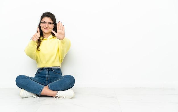 Ragazza russa dell'adolescente che si siede sul pavimento che conta sei con le dita