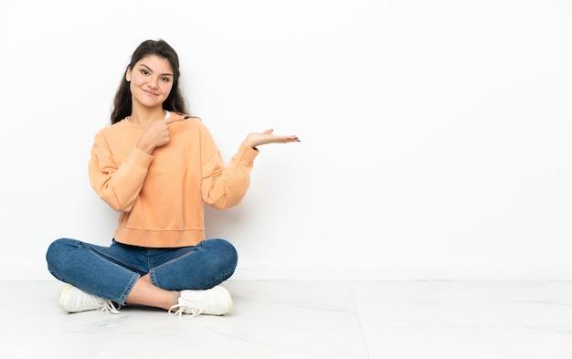Ragazza russa dell'adolescente che si siede sul pavimento che tiene il copyspace sul palmo per inserire un annuncio