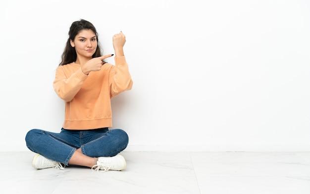 Ragazza russa dell'adolescente che si siede sul pavimento che fa il gesto di essere in ritardo