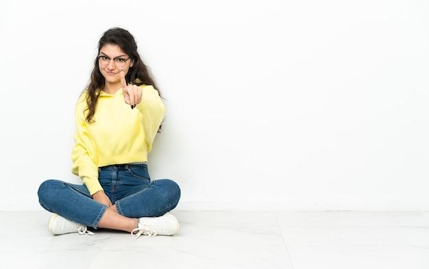 Ragazza russa dell'adolescente che si siede sul pavimento che mostra e che alza un dito