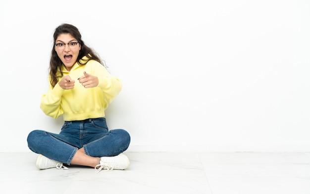 Ragazza russa dell'adolescente che si siede sul pavimento sorpreso e che indica davanti