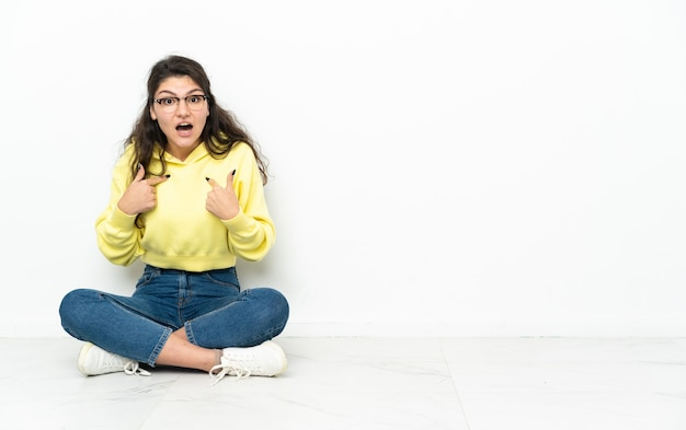 Ragazza russa dell'adolescente che si siede sul pavimento con l'espressione facciale di sorpresa